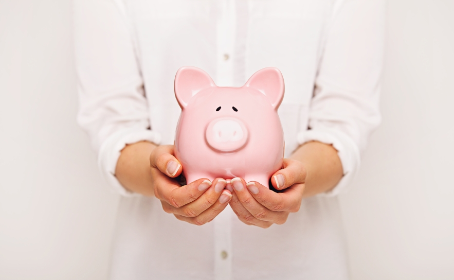 Woman holding a piggy bank with both hands