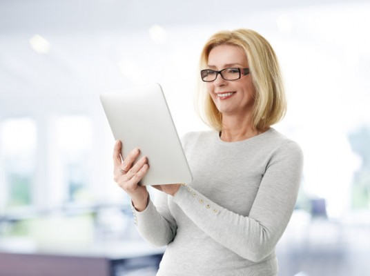 Portrait of mature woman holding digital tablet while standing at office.